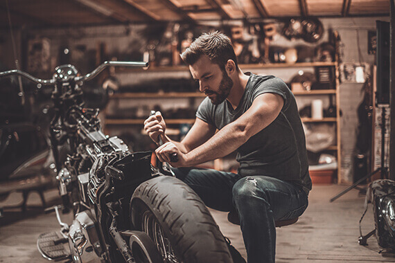 Man repairing his motorcycle in his garage at home