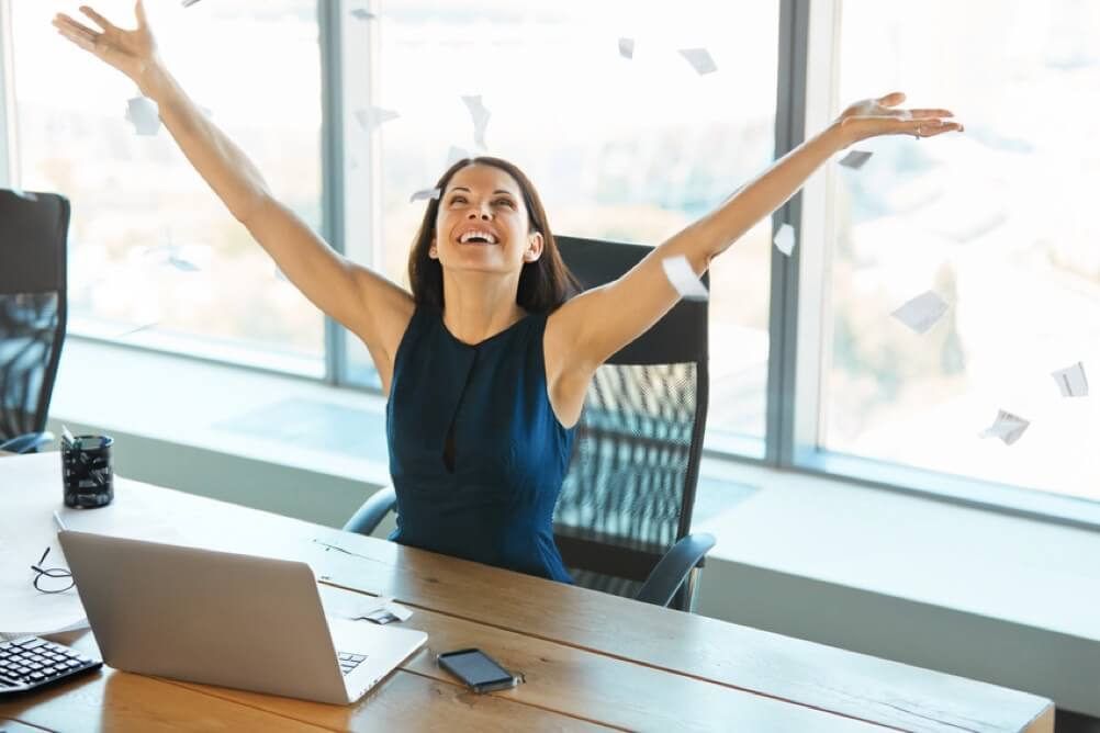 Frau freut sich mit erhobenen Armen, während Papierfetzen auf sie herunterfallen