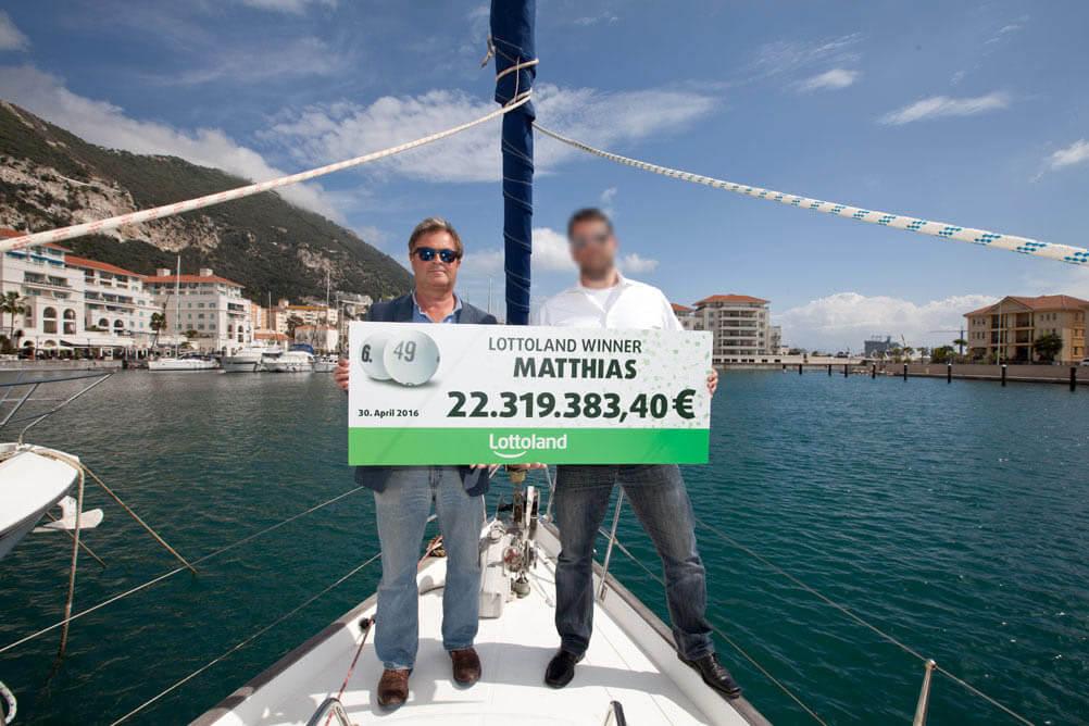 Der Gewinner Matthias und der CEO von Lottoland stehen auf einem Boot und halten einen Scheck mit dem Millionengewinn