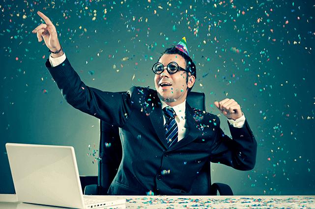 Mann im Anzug und Krawatte feiert mit Partyhut und Konfetti an seinem Schreibtisch