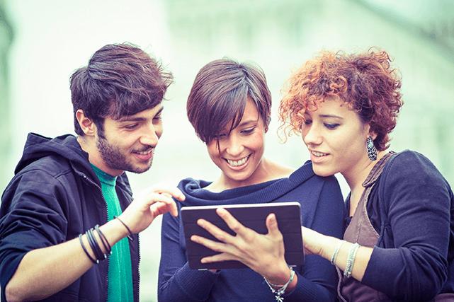 Grupo de pessoas olha para o tablet com alegria