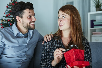 Girl looks unhappy with the Christmas gift from her boyfriend