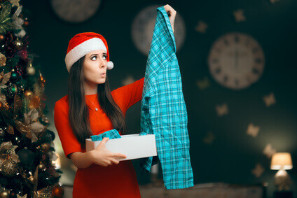 Woman opens a Christmas gift of pyjamas and looks unhappy