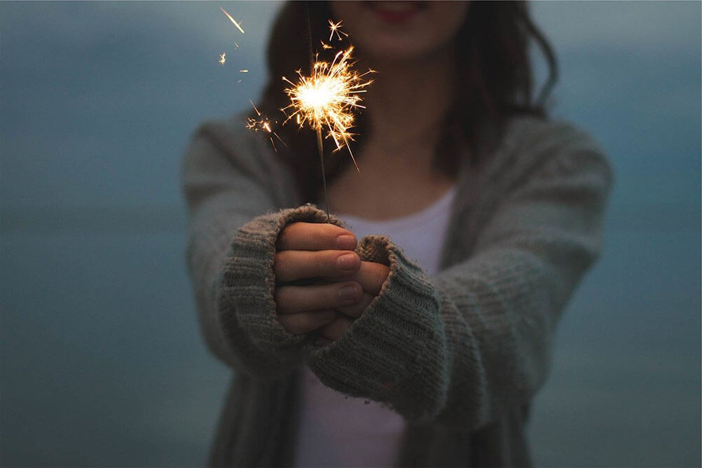 A woman holds a sparkler in her hands while celebrating New Year's Eve