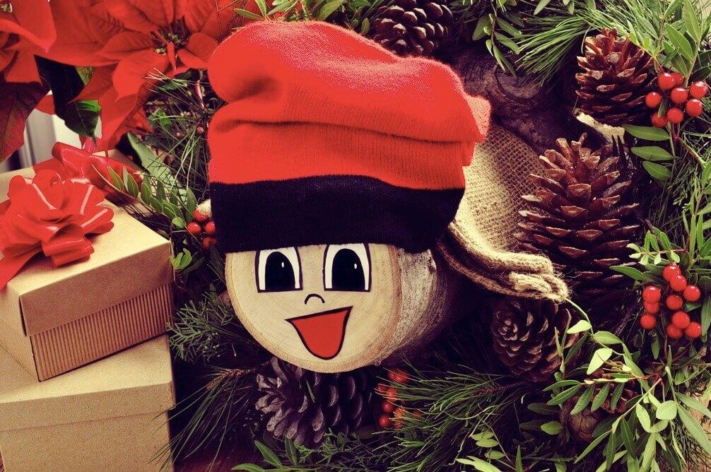 Mit einem lächelnden Gesicht und roter Mütze geschmückter Baumstamm