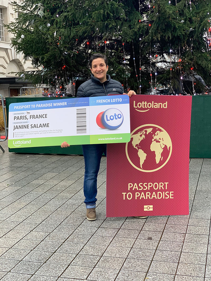 Janine holds up a cheque as a winner of the Lottoland Passport to Paradise competition