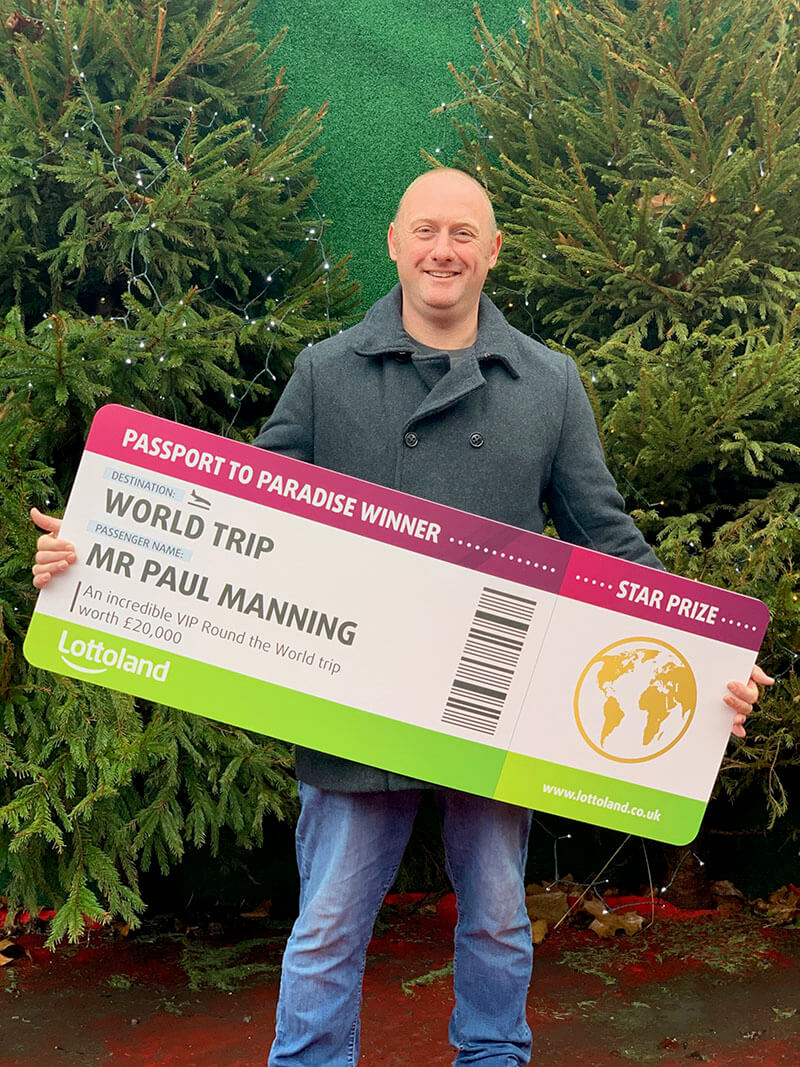 Paul Manning, a firefighter from London, holds up winner's cheque from Lottoland's Passport to Paradise competition