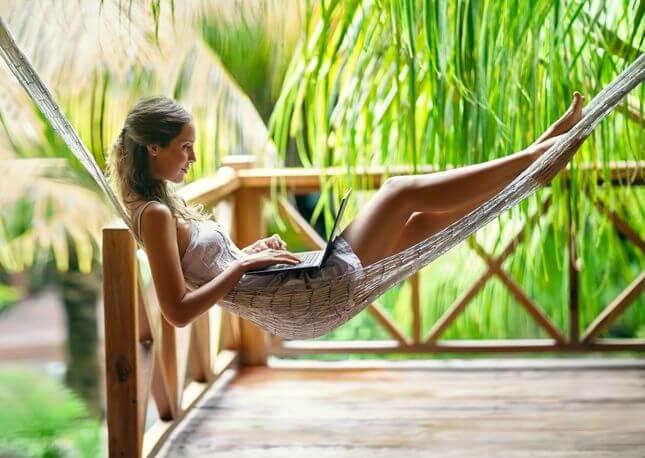 Eine Frau entspannt sich in einer Hängematte, während sie als digitaler Nomade arbeitet