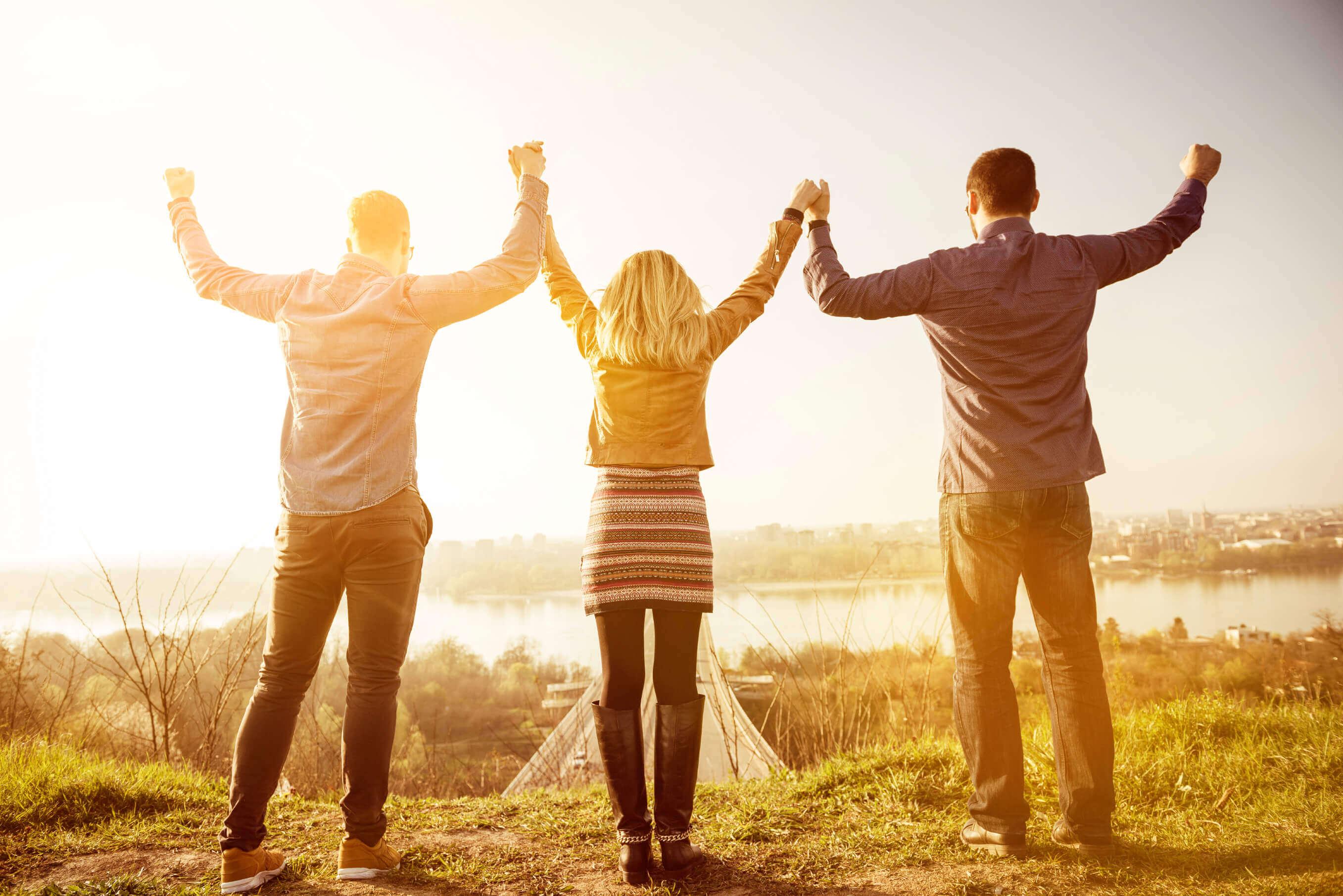 Três pessoas levantam suas mãos com entusiasmo