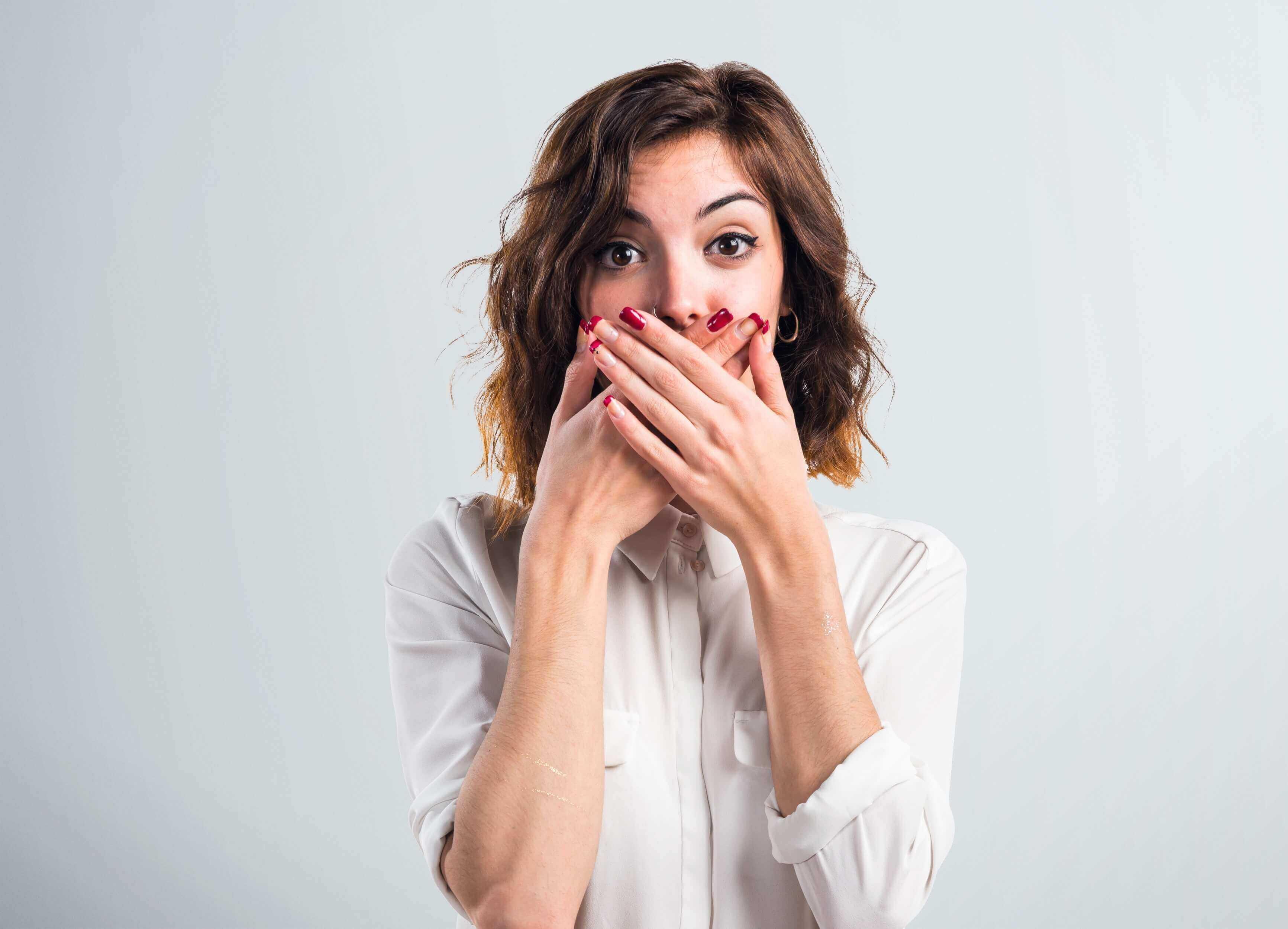 Mulher cobre a boca de surpresa