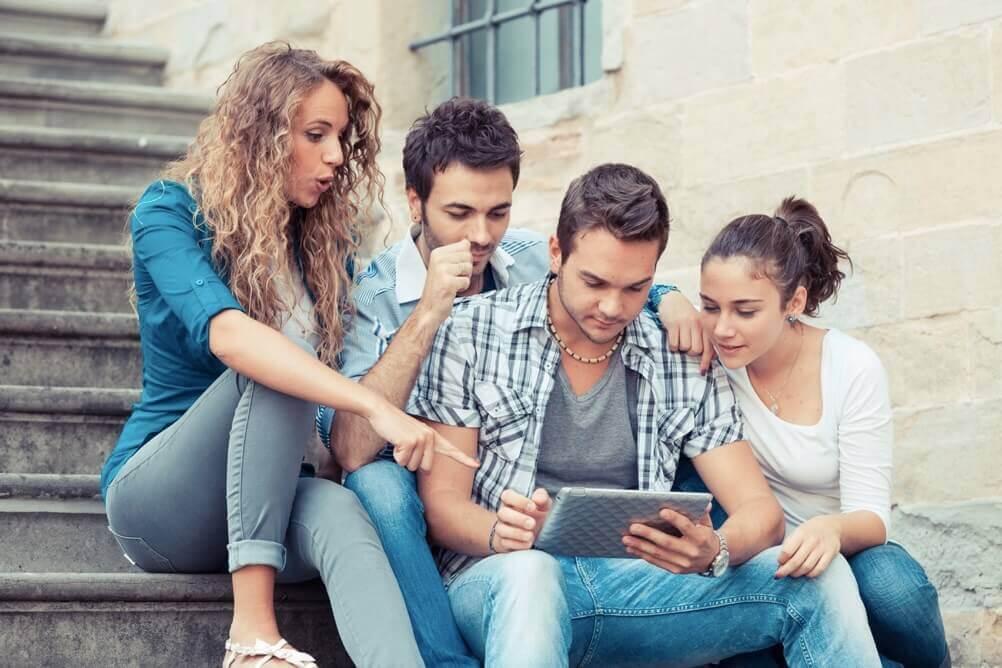 Vier Freunde sitzen auf einer Treppe und schauen gemeinsam auf ein Tablet