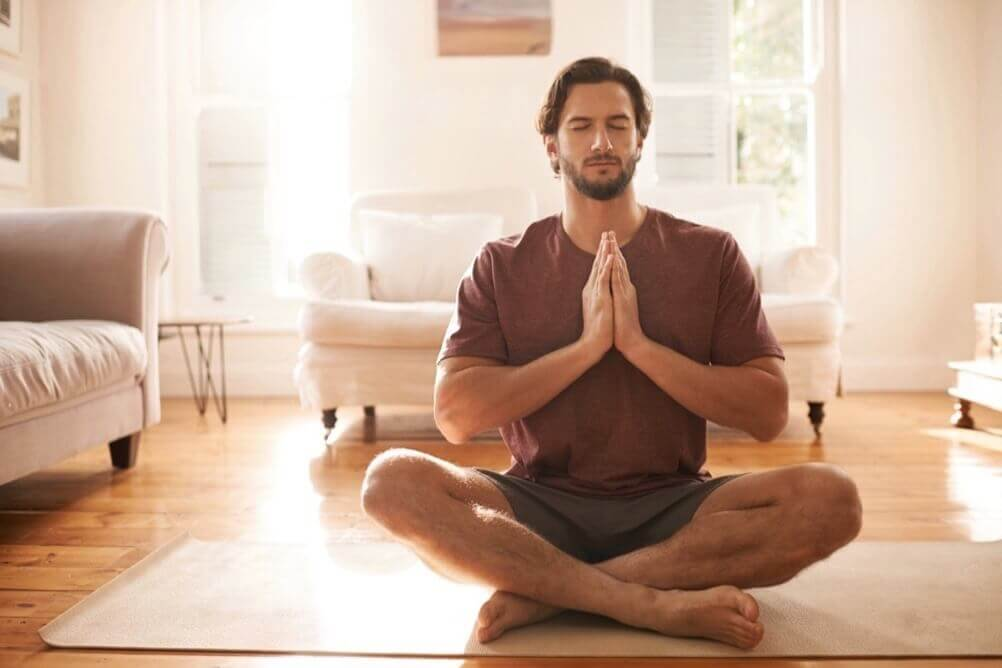 Um homem barbudo praticando ioga em casa