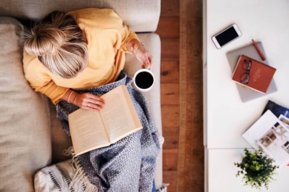 Uma mulher loira lendo um livro em casa