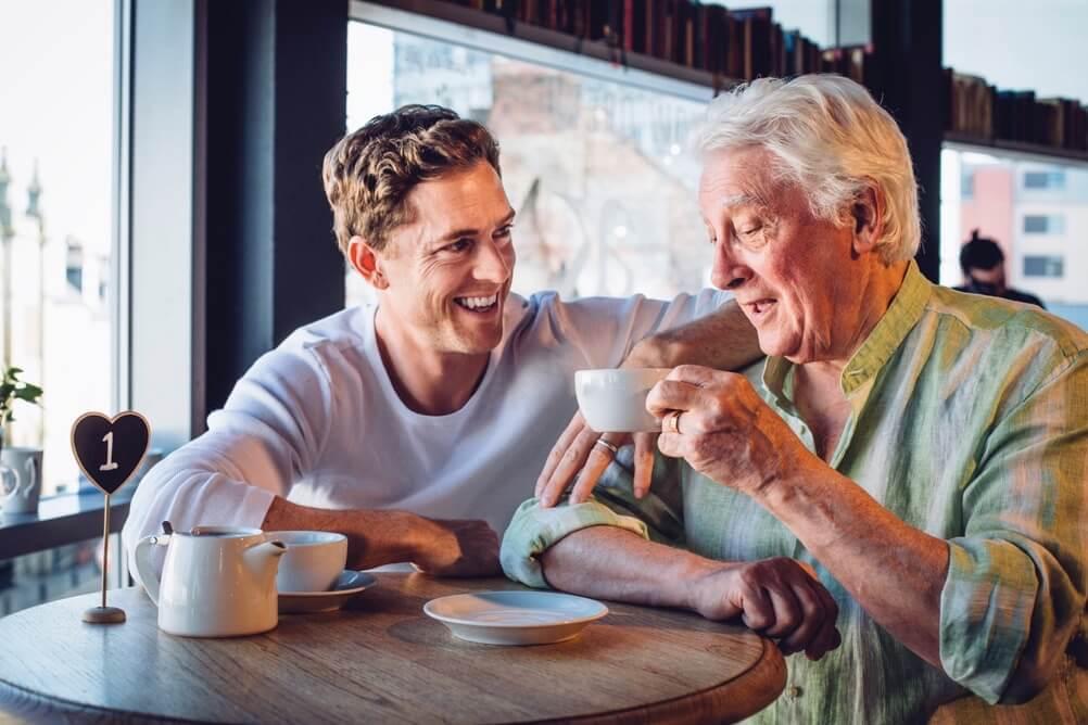 Sohn trinkt lachend mit seinem Vater Kaffee in einem Café