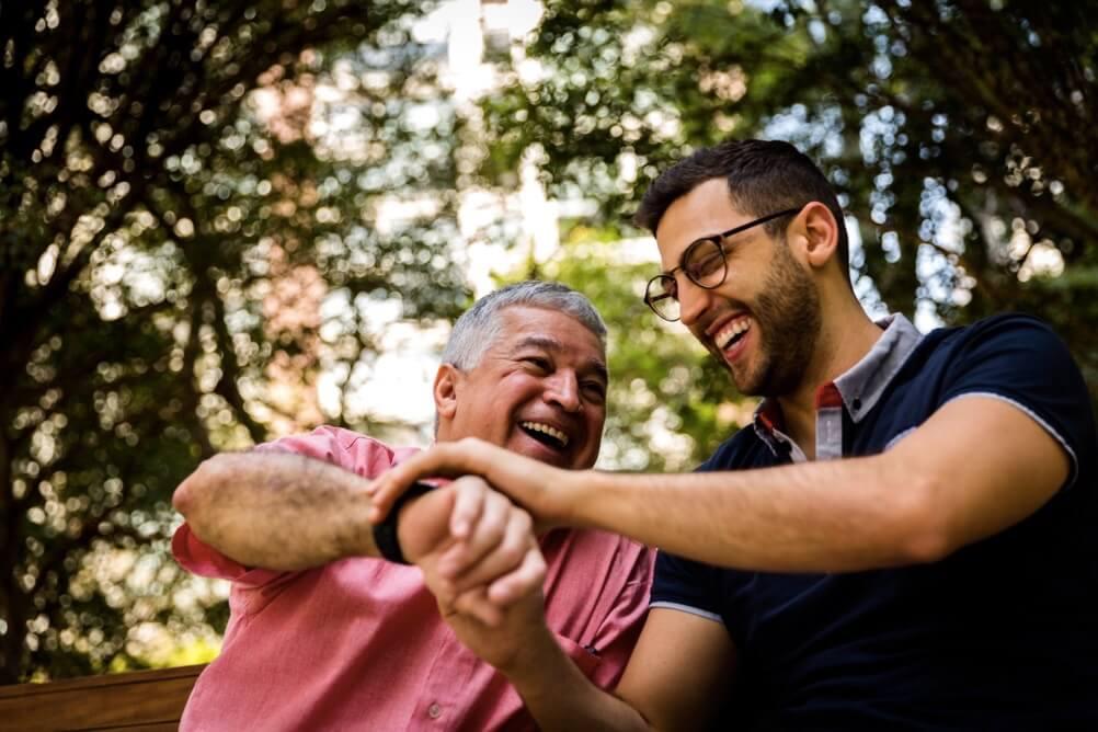 Vater zeigt seinem Sohn seine Uhr, die er zum Vatertag geschenkt bekommen hat