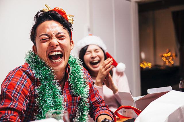 微笑むカップルがクリスマスのおかしな伝統に微笑む